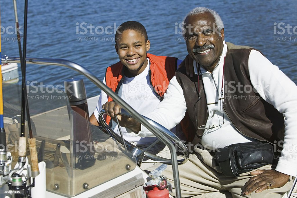 Grandfather Taking Grandson Fishing in Boat stock photo