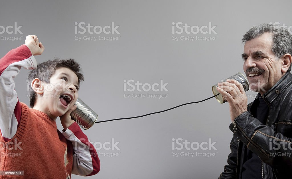 Grandfather talking to grandson on tin can phone royalty-free stock photo