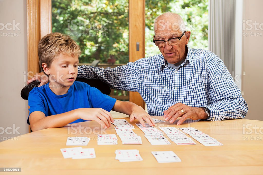 Grandfather Teaching Grandson Solitaire Playing Card Game stock photo