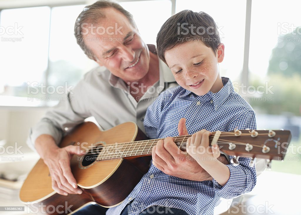Grandfather teaching grandson to play the guitar stock photo