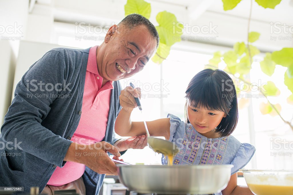 Grandfather teaching his granddaughter to cook stock photo