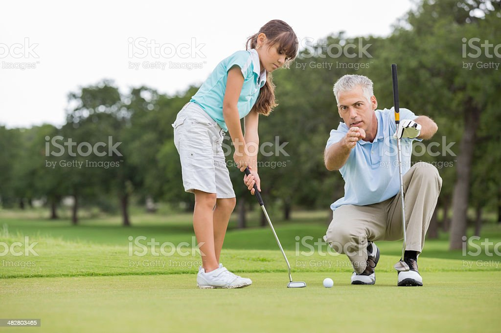 Grandfather teaching little girl to play golf stock photo