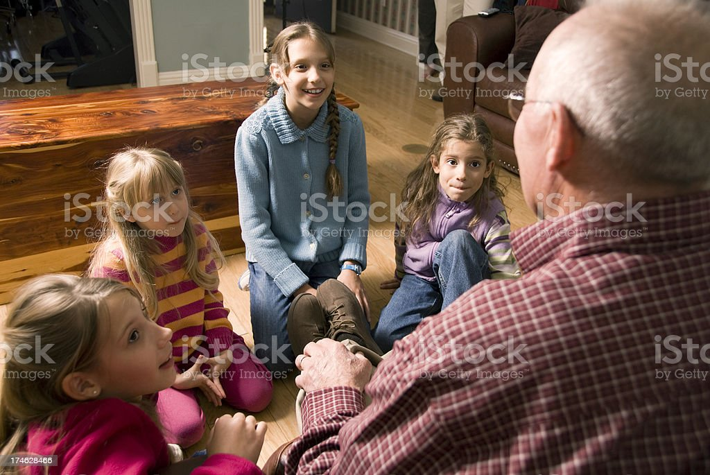 Grandfather telling a story to Grandchildren stock photo