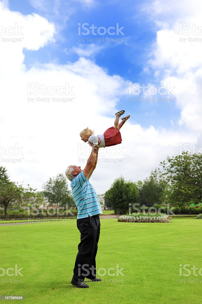 grandfather throwing his grandaughter in the air royalty-free stock photo