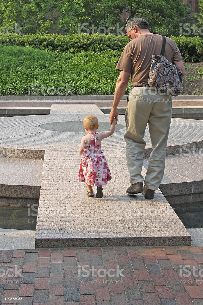 Grandfather walks with young granddaughter royalty-free stock photo