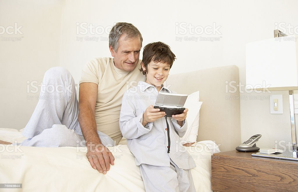 A grandfather watching his grandson play a handheld game royalty-free stock photo