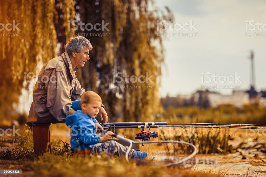 Grandfather with a  grandson on fishing. stock photo