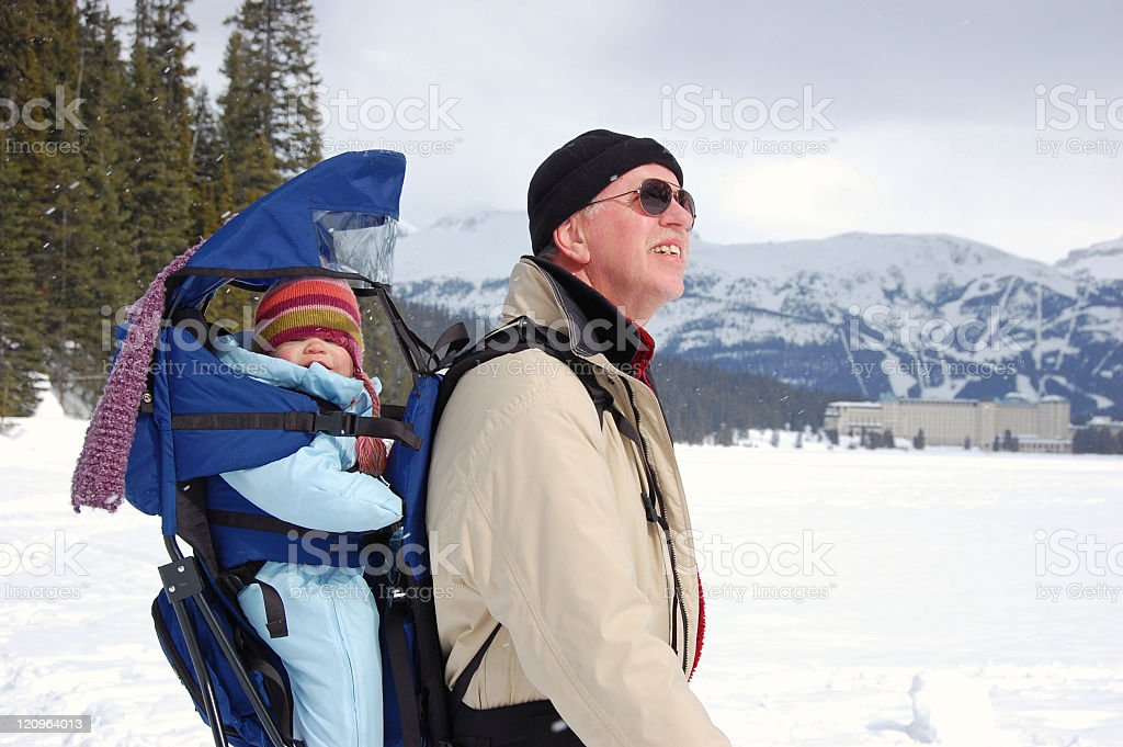 Grandfather with baby grandchild hiking on  frozen Lake Louise,Canada stock photo