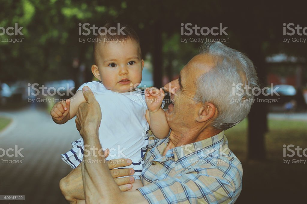 Grandfather with baby in park stock photo