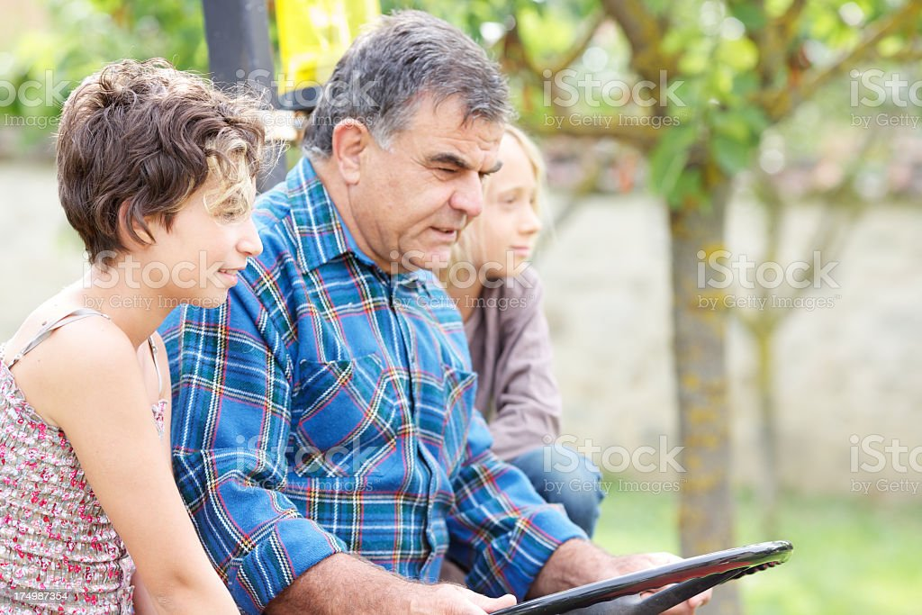 Grandfather with grandchildren on the tractor royalty-free stock photo