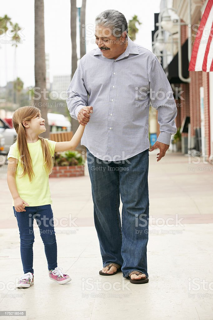 Grandfather With Granddaughter Walking Along Street royalty-free stock photo