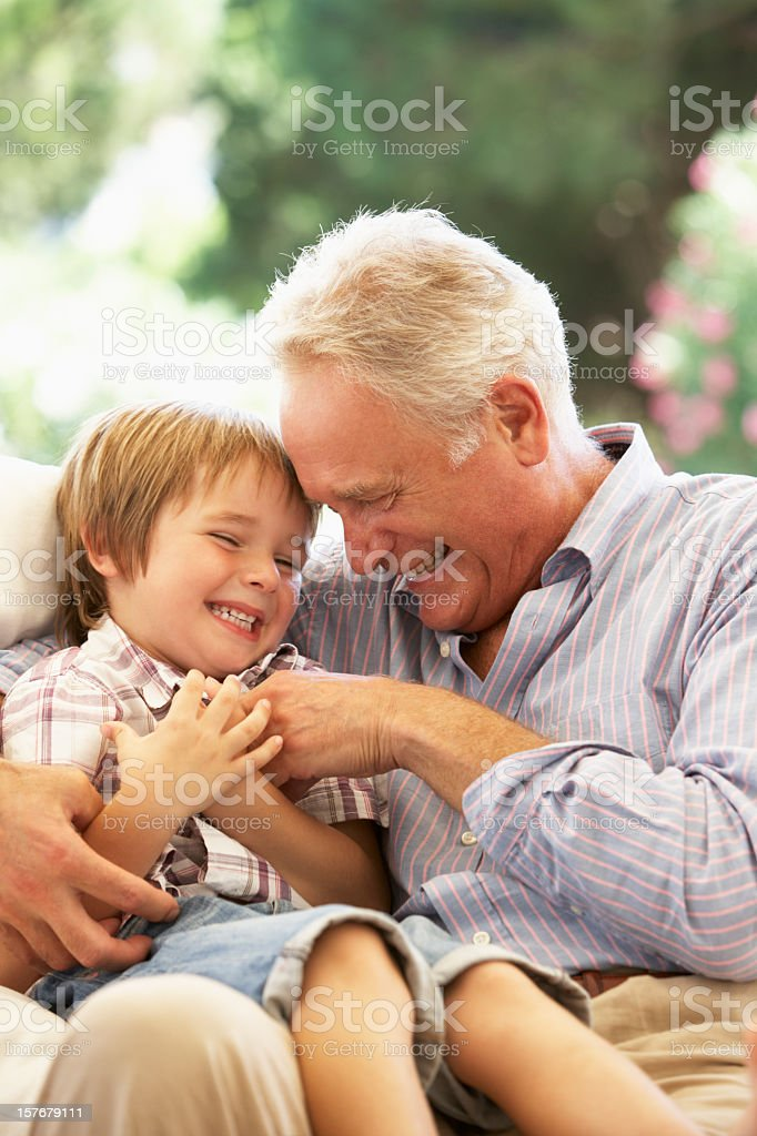 Grandfather With Grandson Laughing Together On Sofa stock photo