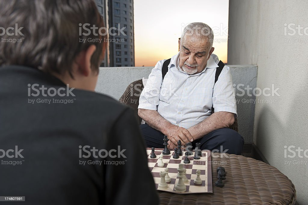 Grandfather with grandson playing chess royalty-free stock photo