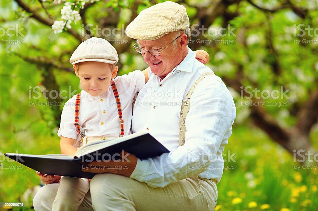 grandfather with grandson reading book in spring garden stock photo
