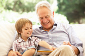 Grandfather With Grandson Reading On Sofa
