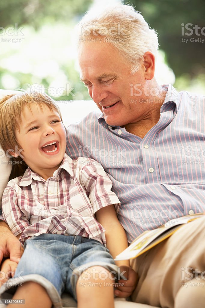Grandfather With Grandson Reading Together On Sofa royalty-free stock photo