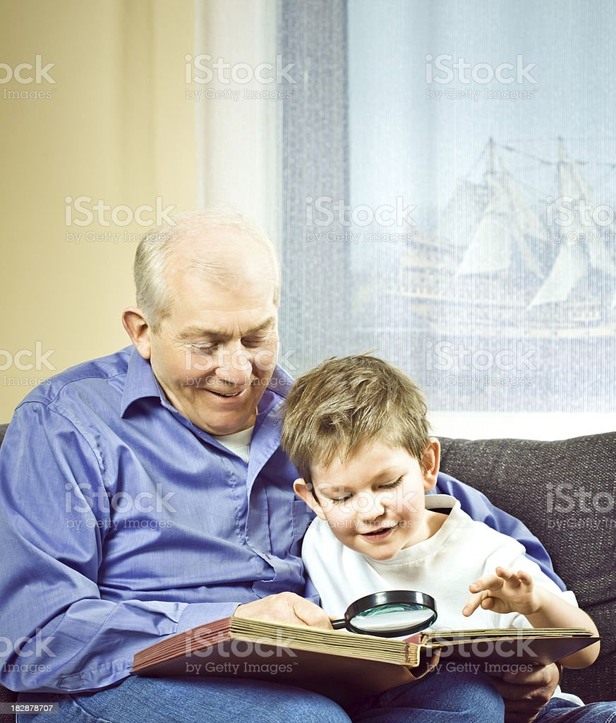 Grandfather with grandson watching stamps stock photo
