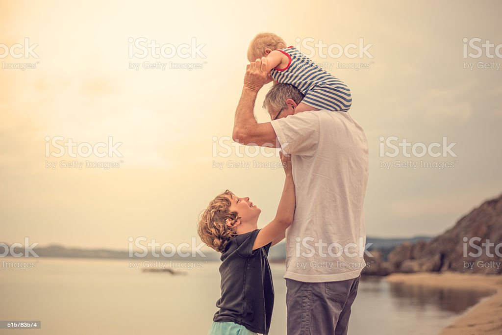 Grandfather with his grandchildren at the beach stock photo
