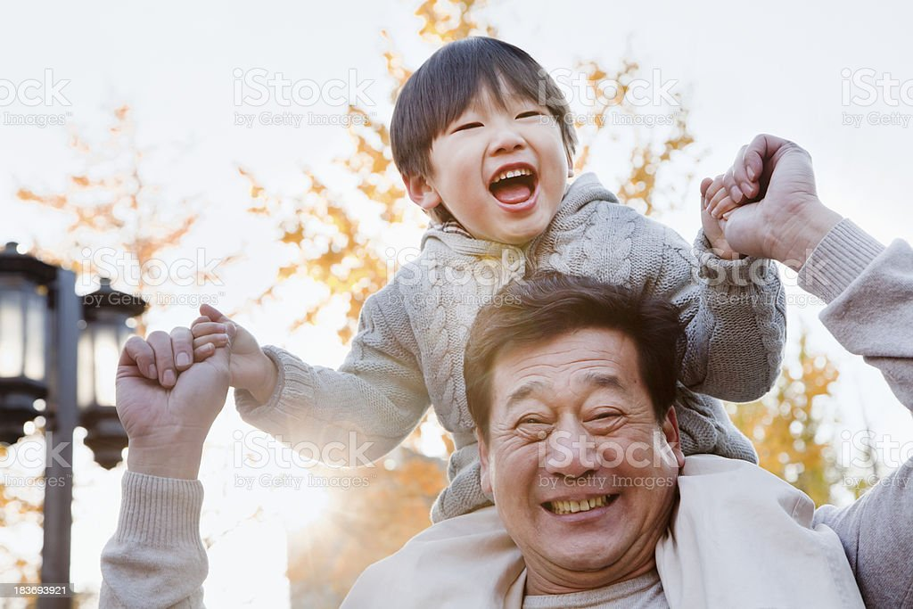 A grandfather with his grandson on his shoulders stock photo