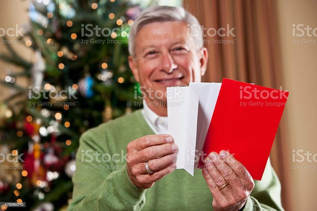Grandfather with holiday cards by Christmas tree royalty-free stock photo