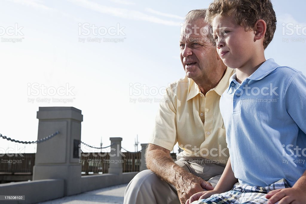 Grandfather with little boy watching together stock photo