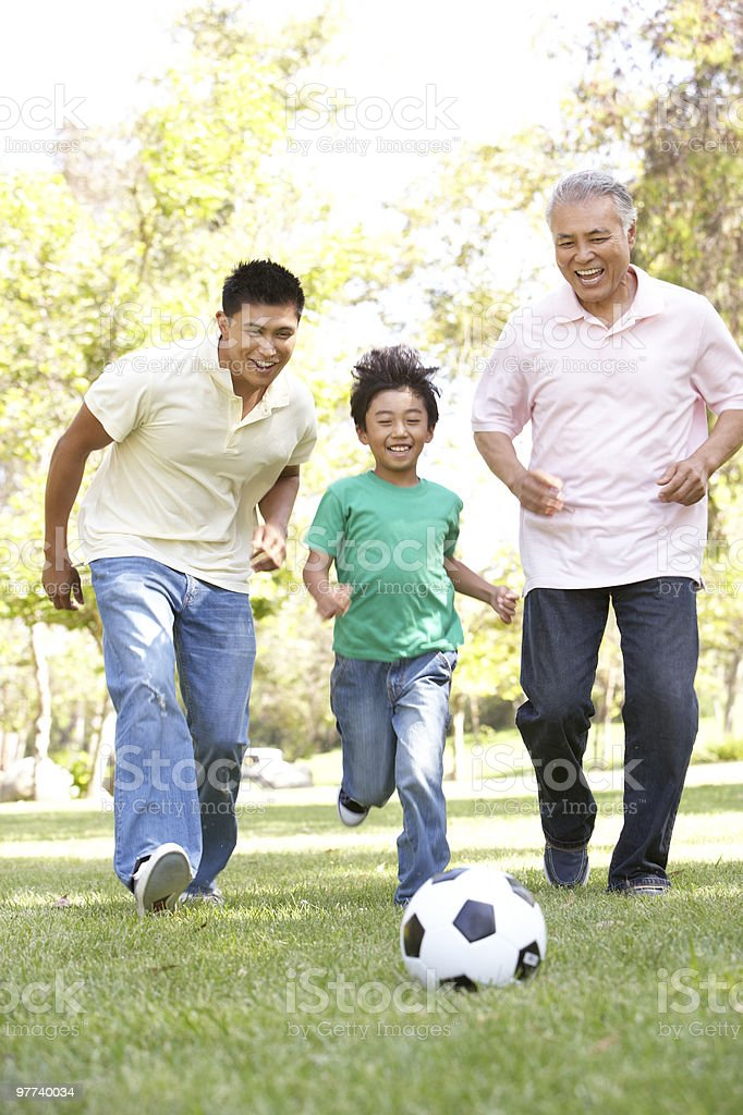 Grandfather With Son And Grandson Playing Football stock photo