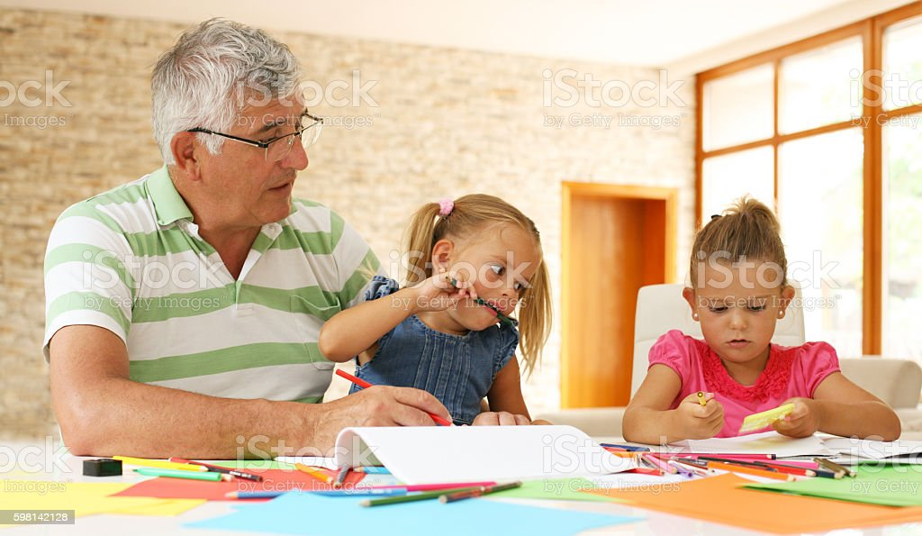 Grandfather working homework with granddaughters. stock photo
