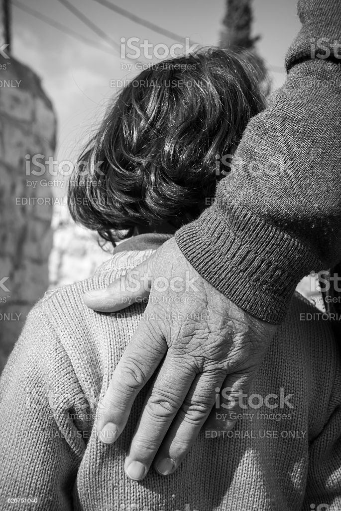 Grandfather's hand on young girl's back in East Jerusalem stock photo