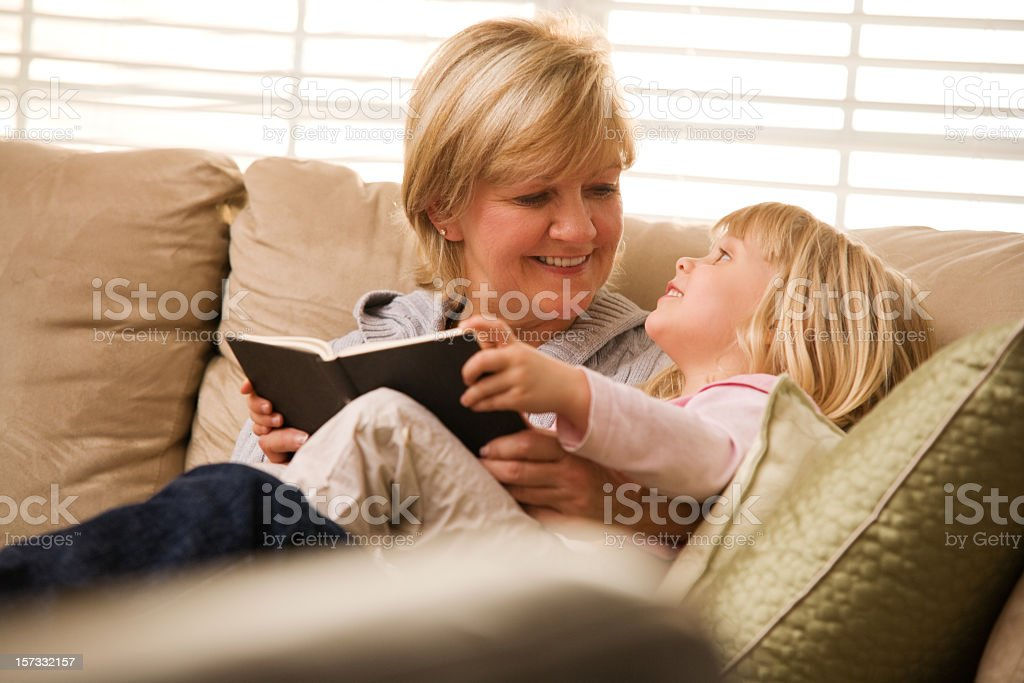 Grandma and granddaughter reading a book on the couch royalty-free stock photo