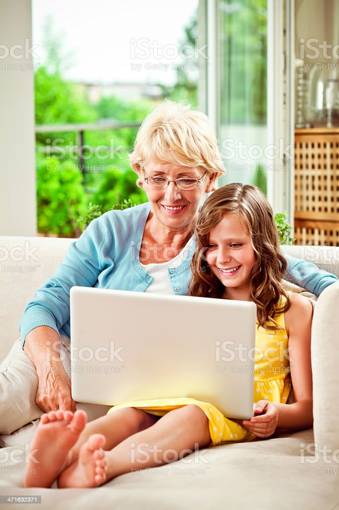 Grandma and granddaughter with laptop royalty-free stock photo