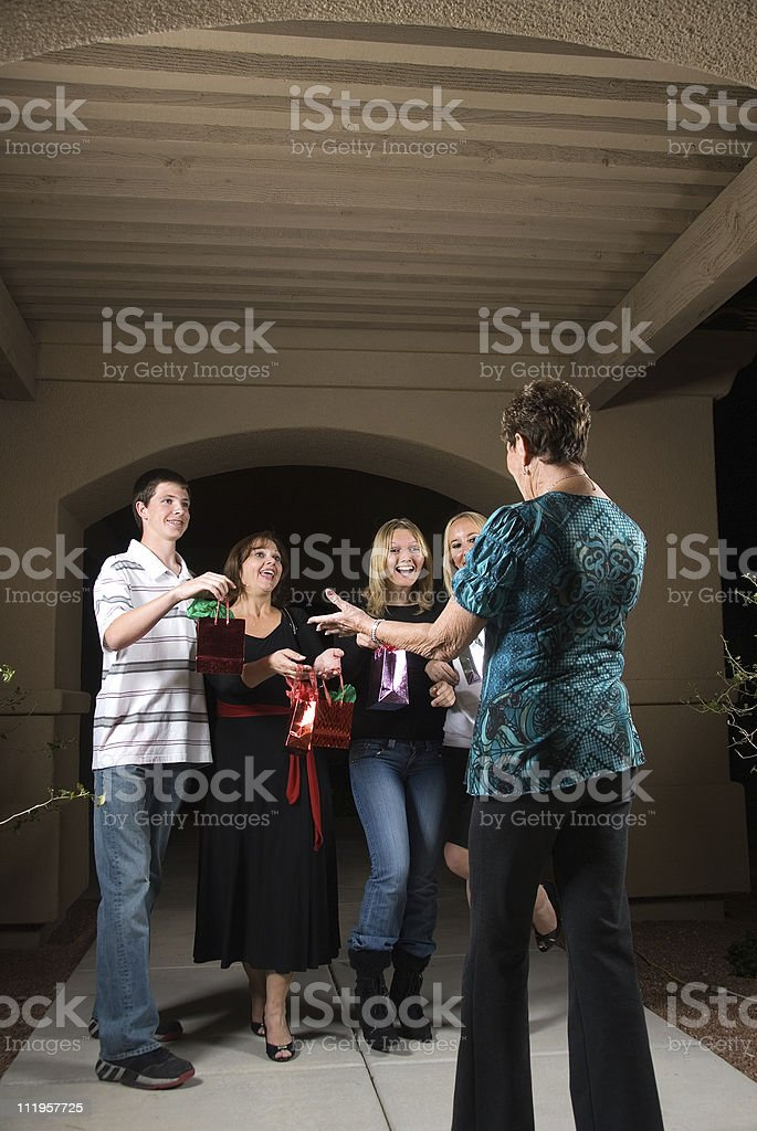 Grandma greating visitors the driveway holding presents stock photo