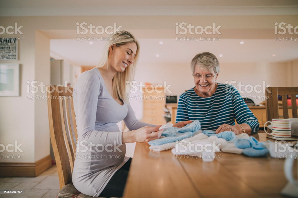 Grandma Knitting Baby Clothes stock photo