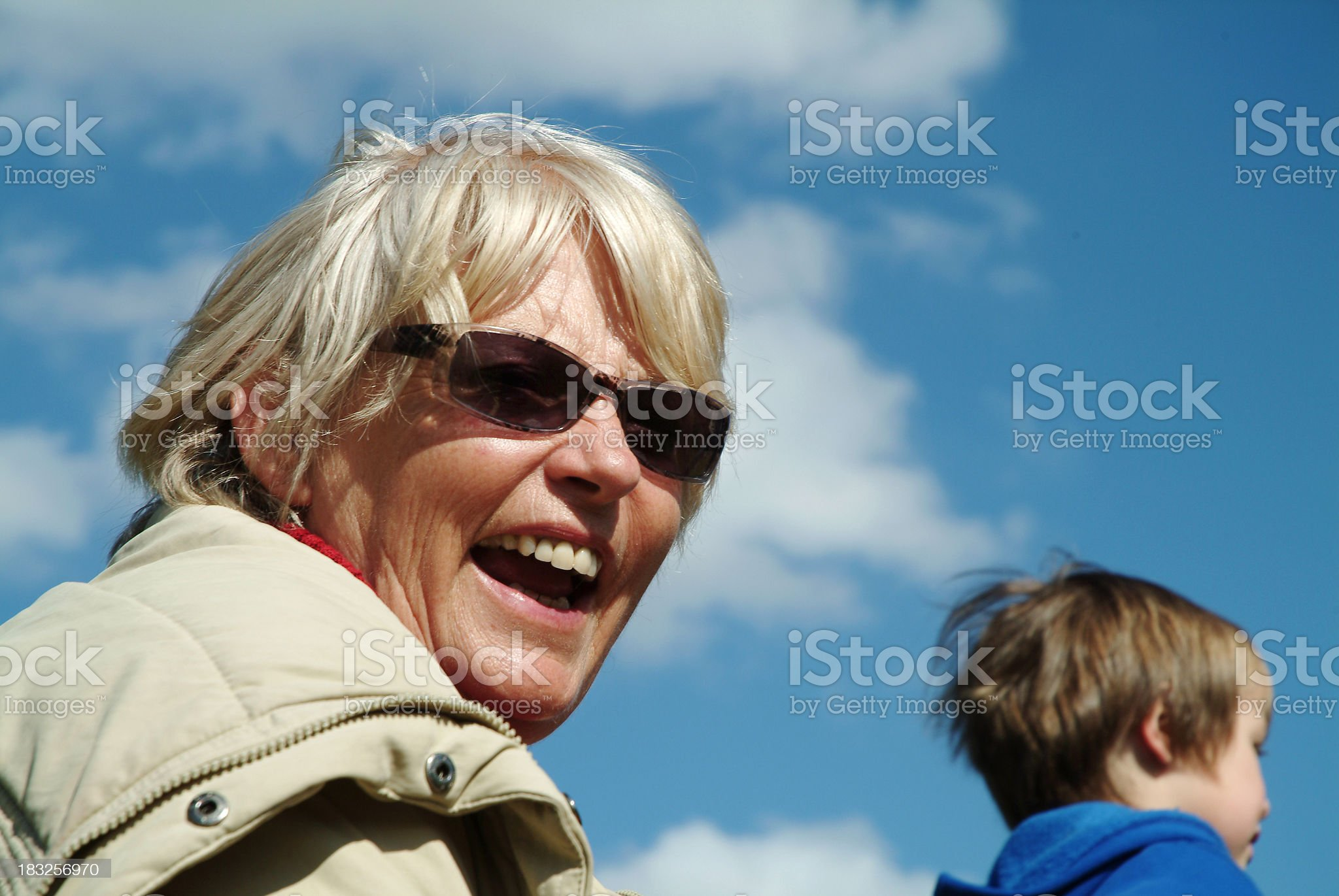 Grandma laughing with grandson against blue sky royalty-free stock photo
