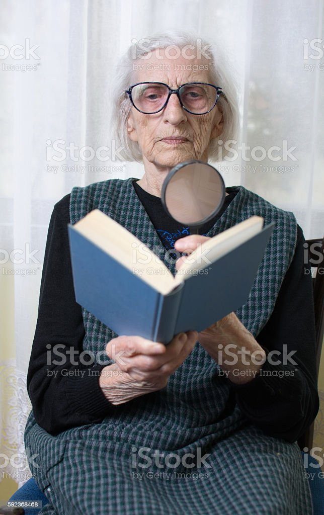 Grandma reading a book through magnifying glass stock photo