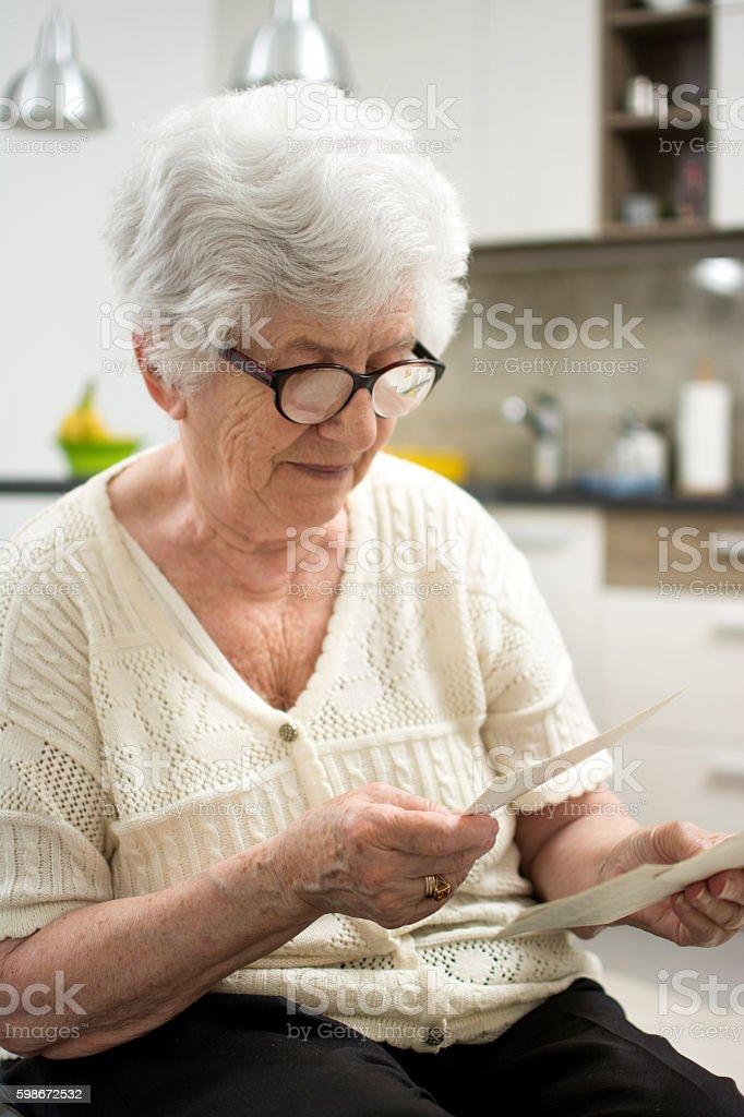 Grandma sitting at home and looking at old photos. stock photo