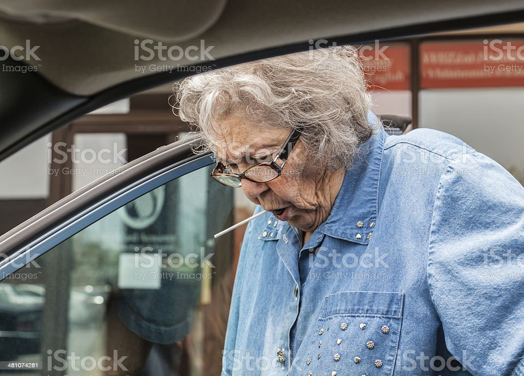 Grandma Sucking Lollypop While Getting Into Car royalty-free stock photo