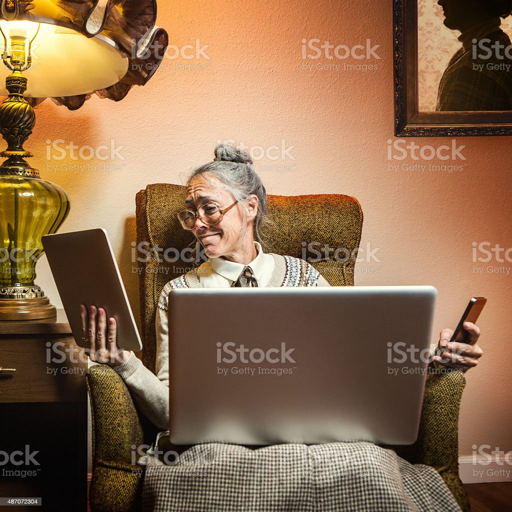 Grandma Using Multiple Modern Electronics stock photo