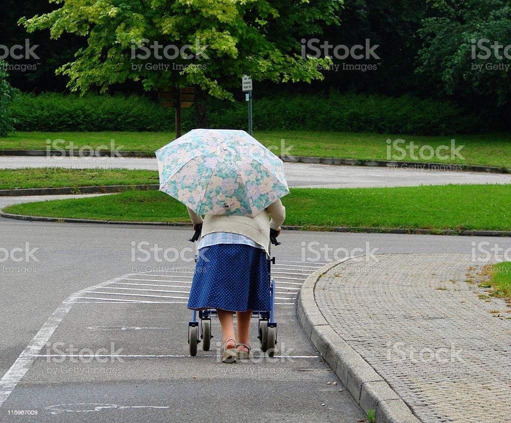 Grandma walking in the rain stock photo