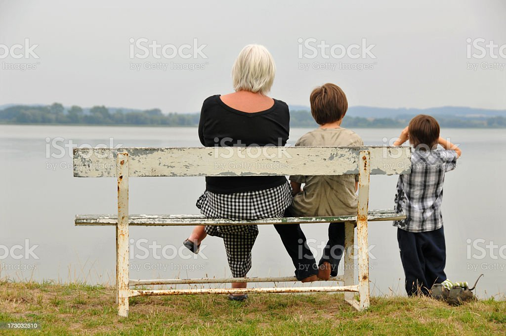 Grandma with grandsons on a bench at the waterfront royalty-free stock photo