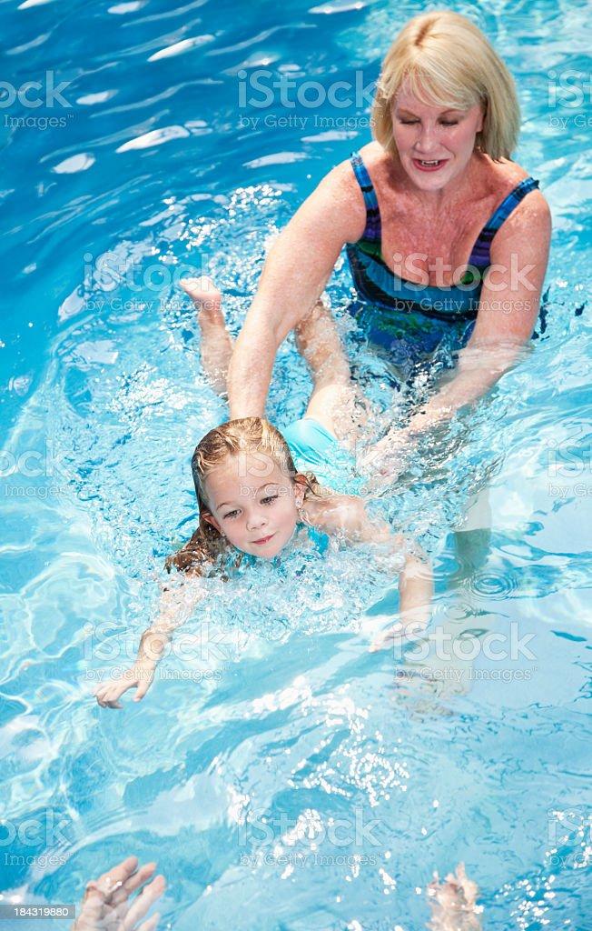 Grandma with little girl swimming to grandpa royalty-free stock photo