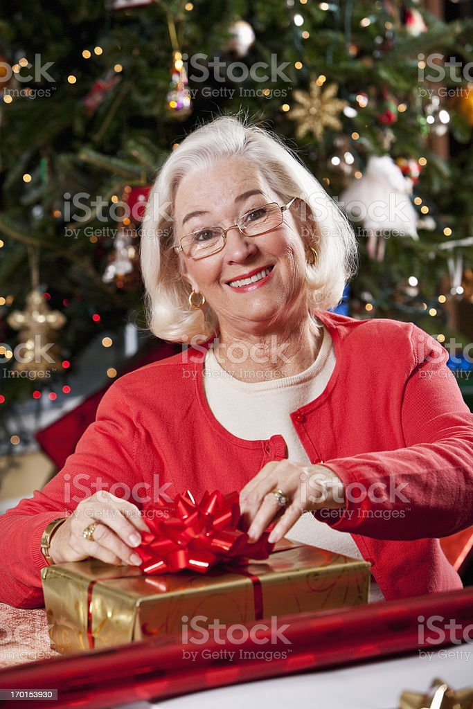 Grandma wrapping Christmas gifts by tree stock photo