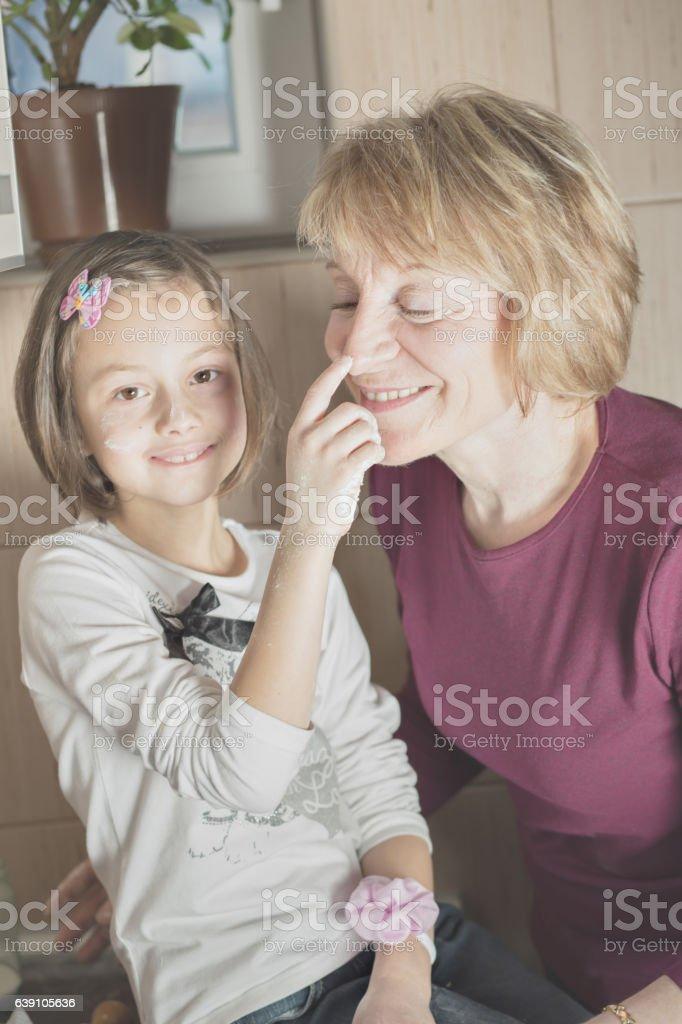 Grandmom and grandchild having fun in kitchen stock photo