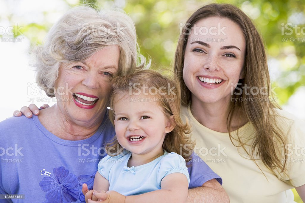 Grandmother adult daughter and grandchild smiling in park royalty-free stock photo