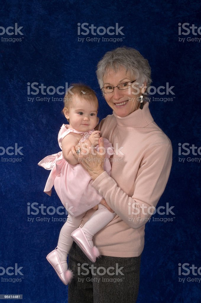 Grandmother and baby girl on blue background. royalty-free stock photo