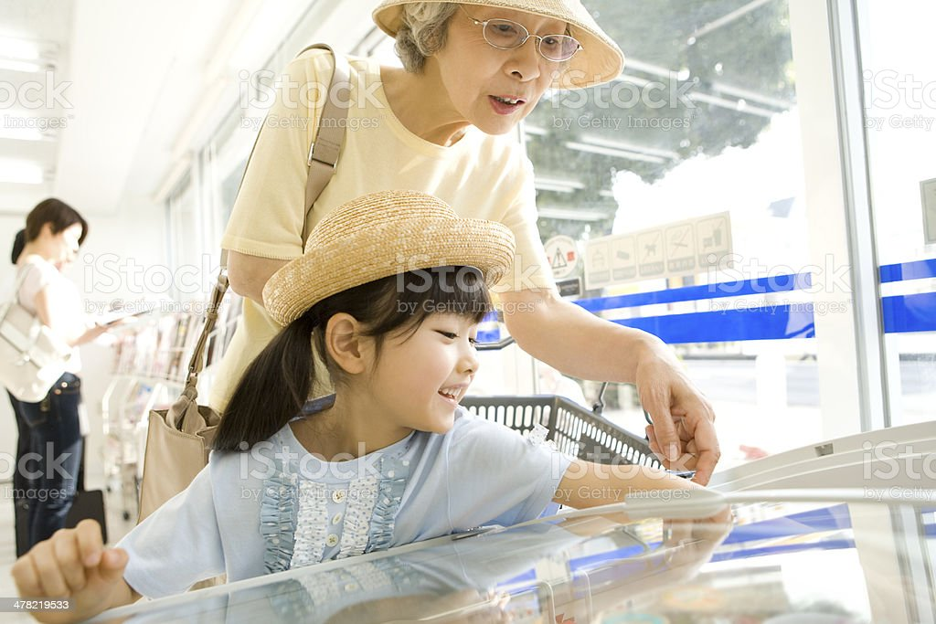 Grandmother and grandchild doing some shopping at convenience store stock photo