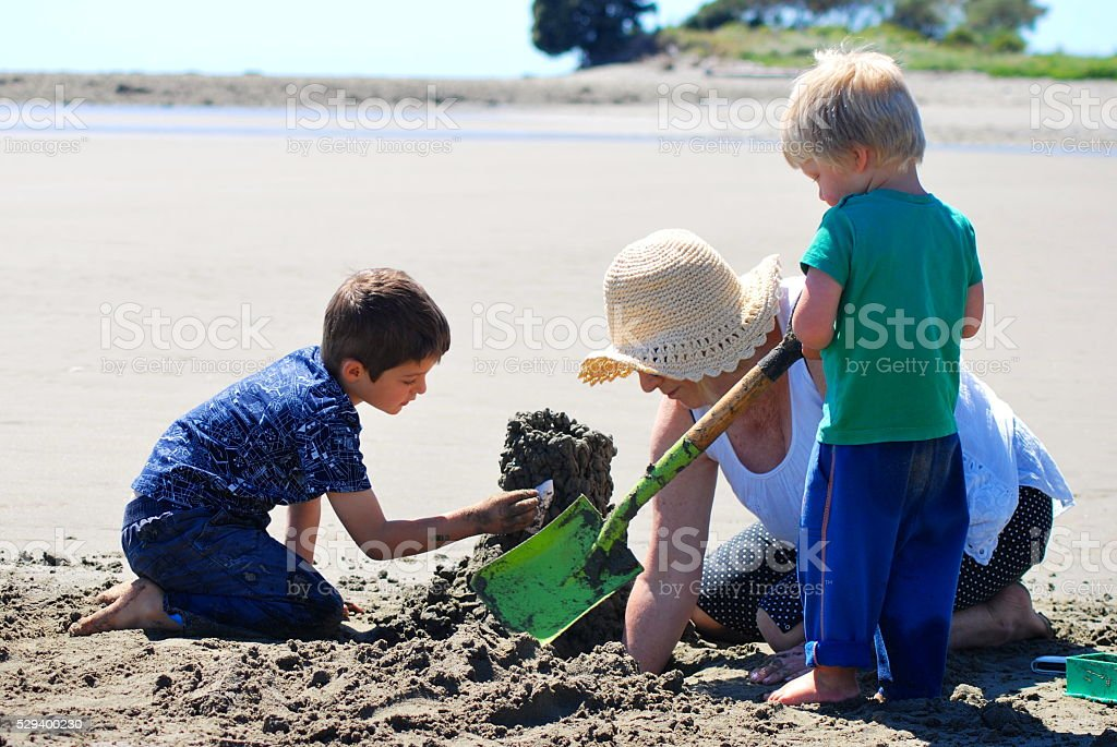 Grandmother and Grandchildren build Sandcastle stock photo