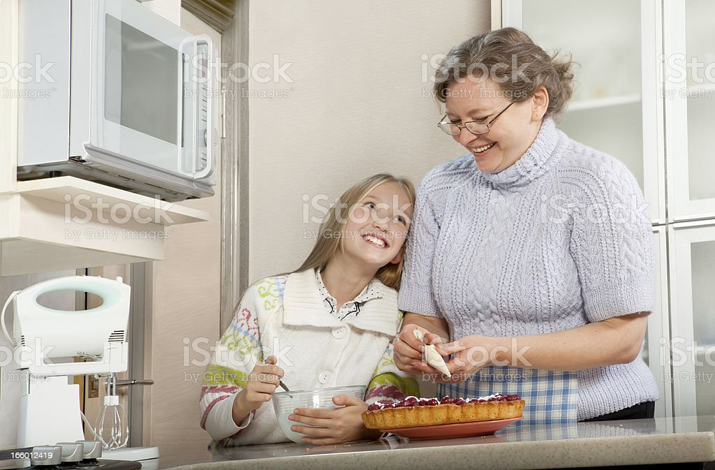 Grandmother and Granddaughter are doing Pie in the Kitchen royalty-free stock photo