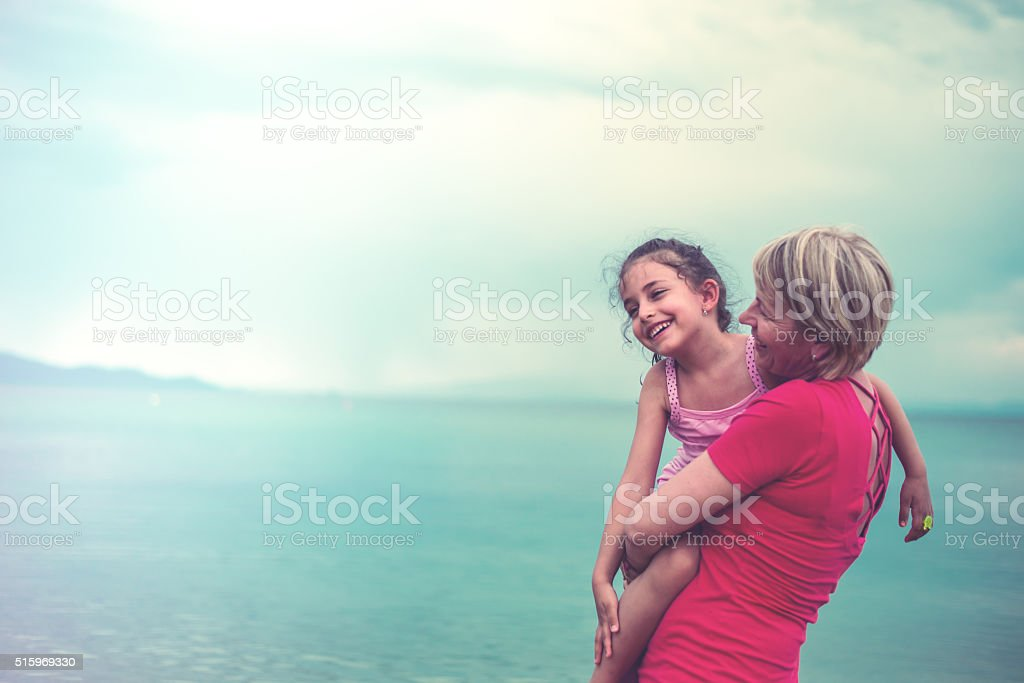 Grandmother And Granddaughter at the beach stock photo