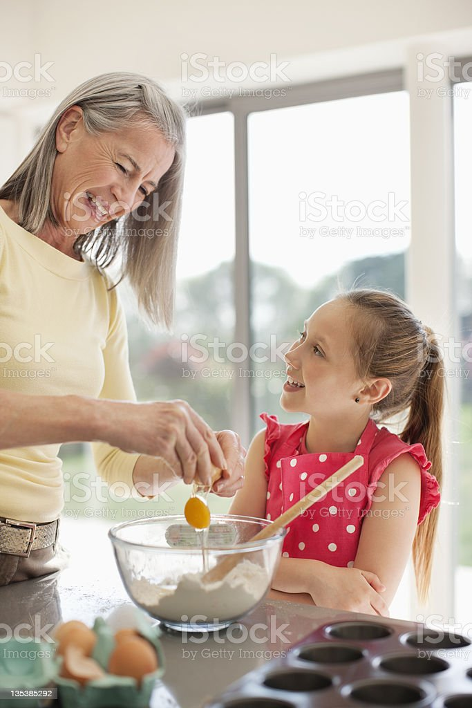 Grandmother and granddaughter baking cupcakes together royalty-free stock photo