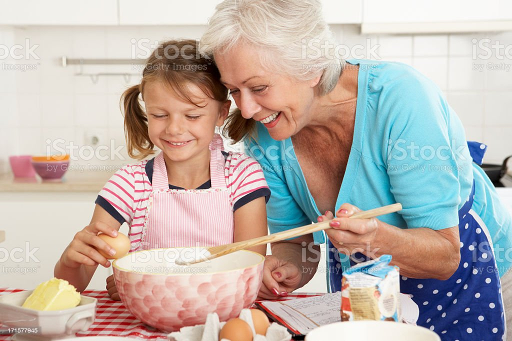 Grandmother and granddaughter baking in kitchen stock photo